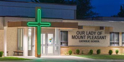 Our Lady of Mount Pleasant School exterior front entrance with cross glowing green at night